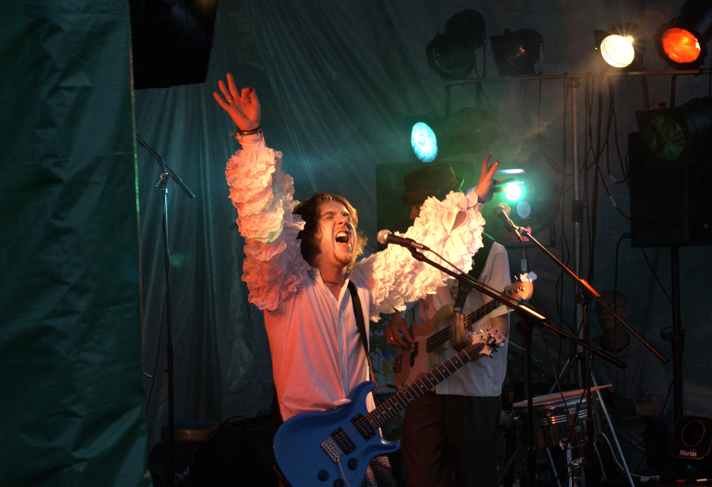Man singing on stage with his arms raised, he has a guitar strapped to him