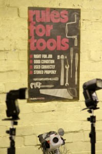 "Two flash guns in front of a poster on a wall which reads ""Rules for tools"""