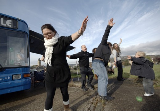 Charity workers dancing in front of a bus