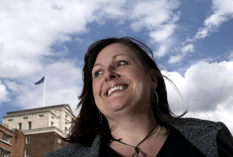 Woman smiling against a cloudy sky and Leeds train station