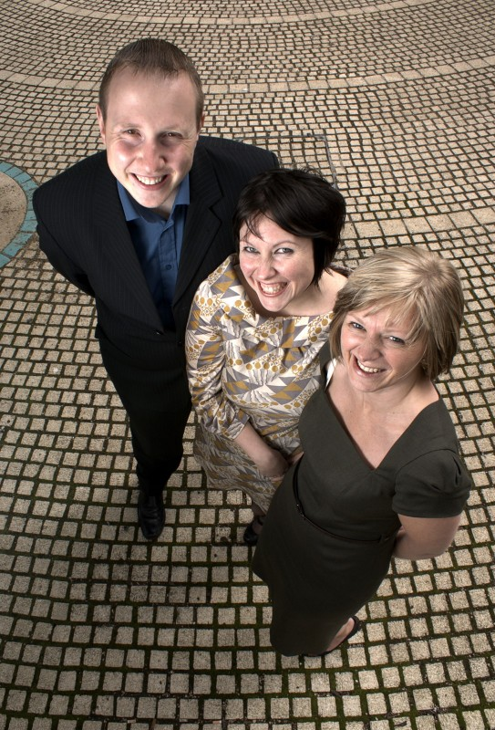 Three people looking up towards the camera and smiling