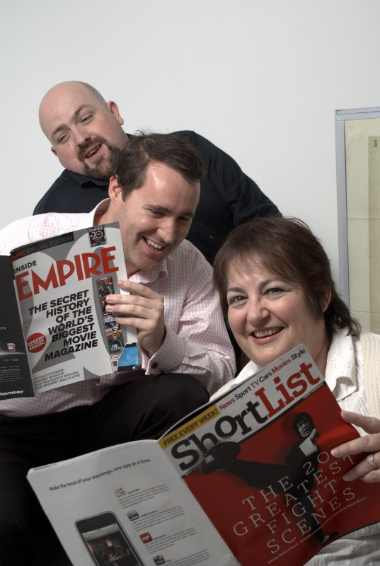 Three people reading magazines and laughing