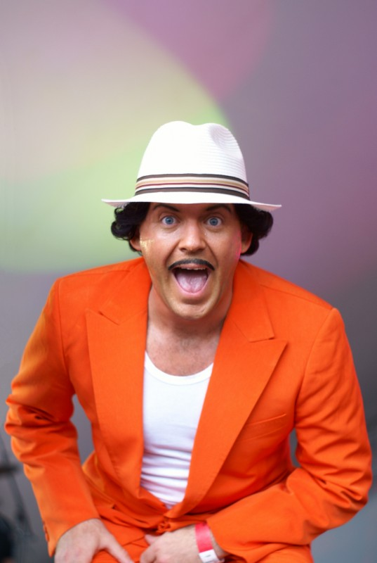 Man smiling with a hat on and orange jacket