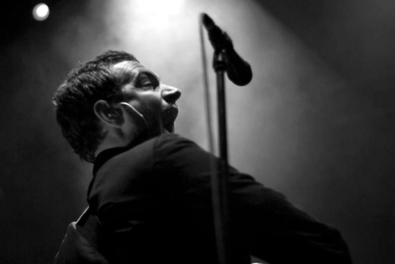 Man plays a guitar behind a microphone