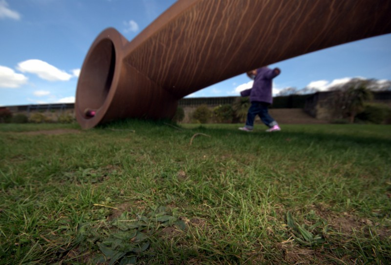 Child playing on some grass behind a sculpture at Yorkshire sculpture park