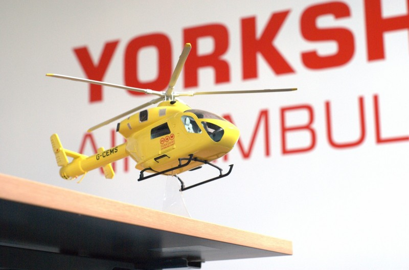 Model of the Yorkshire air ambulance in front of their logo