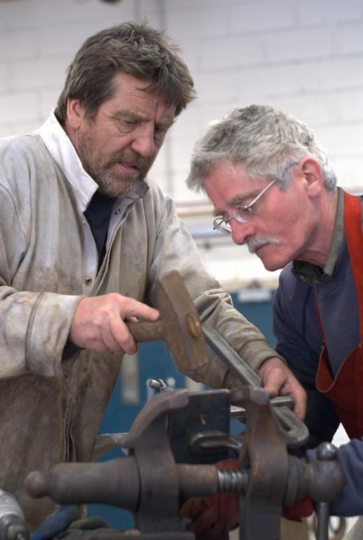 Two men hammering metal at Yorkshire Sculpture Park
