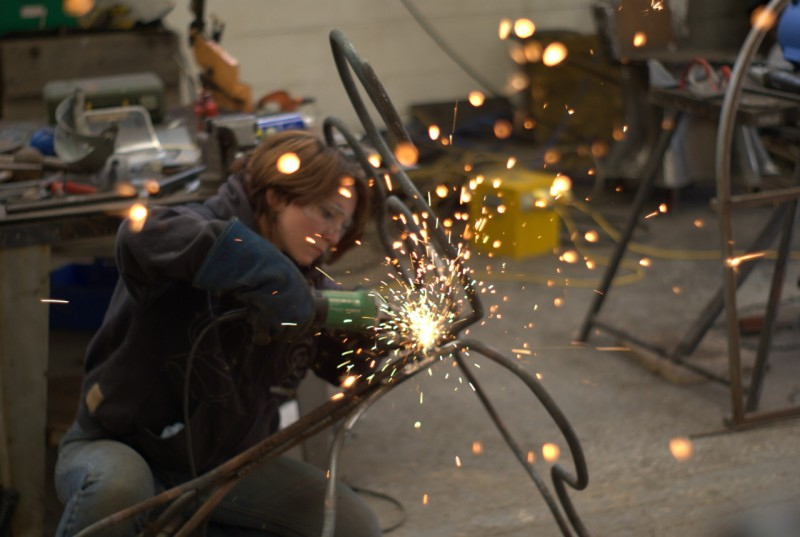 Sparks coming from a woman welding metal