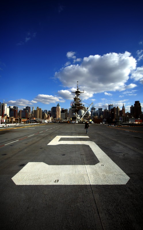 The number '5' painted on the deck of an aircraft carrier moored in front of Manhattan island