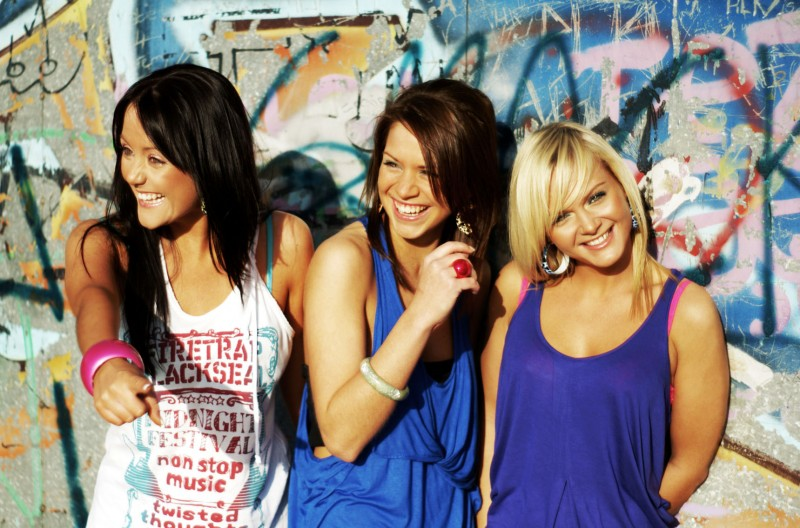 Three girls stood in front of a wall covered in graffiti