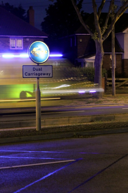 A dual carriage way sign in front of blurred light trails left by a speeding ambulance