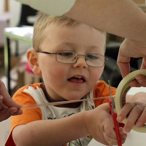 Young child cutting sellotape at a sculpture event
