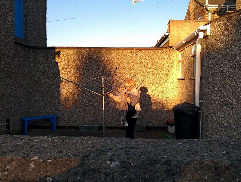 An old woman hangs out her washing in a sunlit backyard in Grimsby