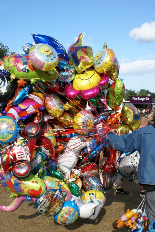 A group of colourful helium balloons held by a vendor