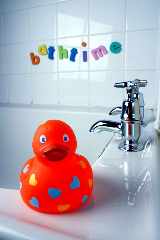 A rubber duck on the edge of a bath next to some taps, behind are letters stuck to some tiles that read 'bath time'