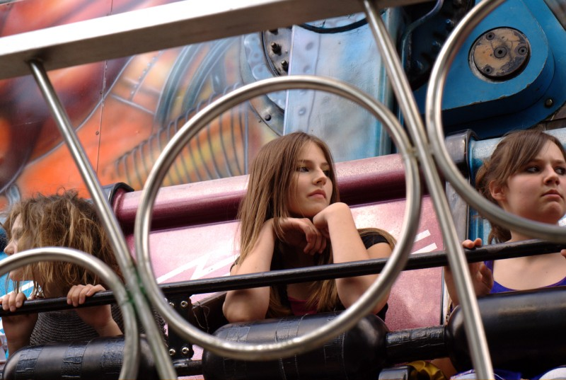A young girl on a fairground ride shot through some railings