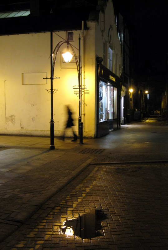 A blurred pedestrian walks through a wet Harrogate street at night