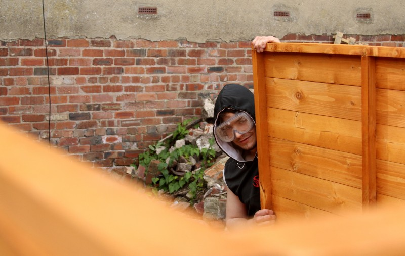 A man peers from behind a shed that is under construction