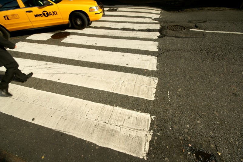 A taxi driving over a pedestrian crossing in New York