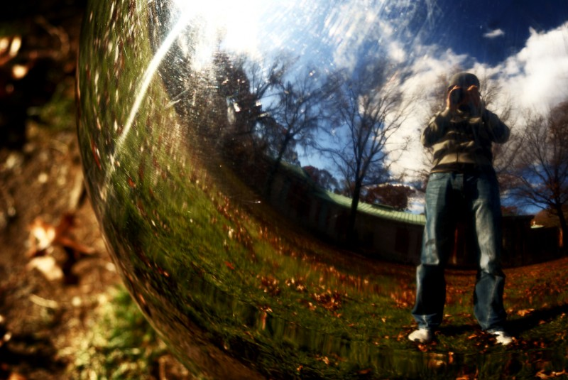 Reflection of a photographer in a silver orb in a park in New York