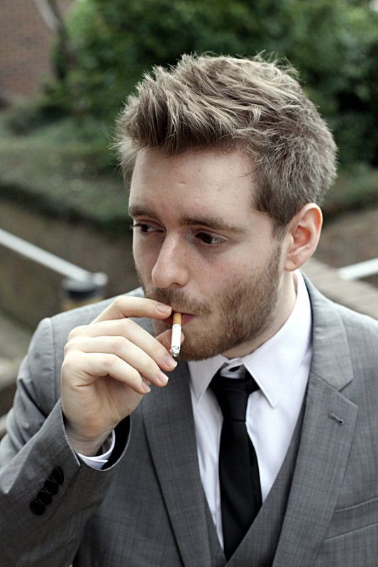 Man in a suit smoking a cigarette at a hotel in Lawnswood in Leeds