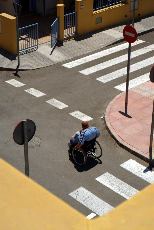 A man in a wheelchair crossing a road junction