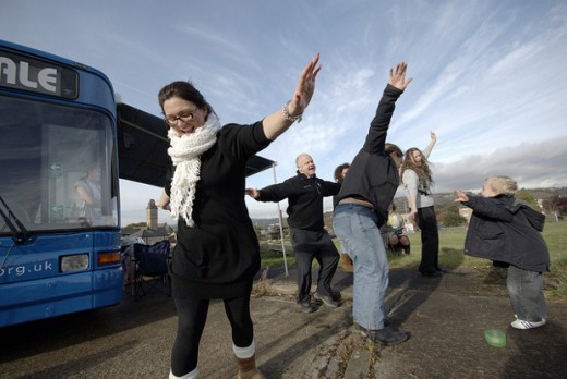 People dancing in front of a bus