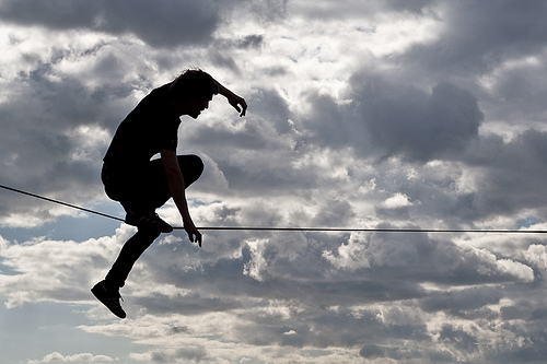 Man balancing carefully on a tightrope against the sky