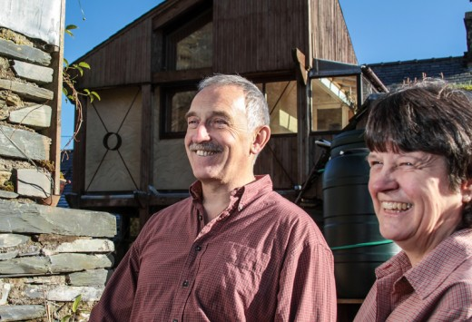 Man and woman smiling in front of an eco guest house