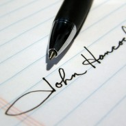Pen signing a signature on lined paper