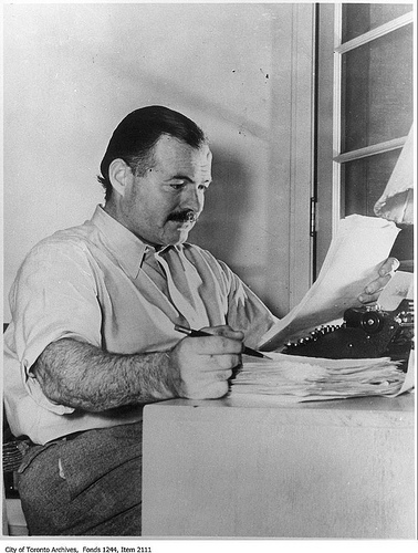 Ernest Hemingway sat writing at a desk
